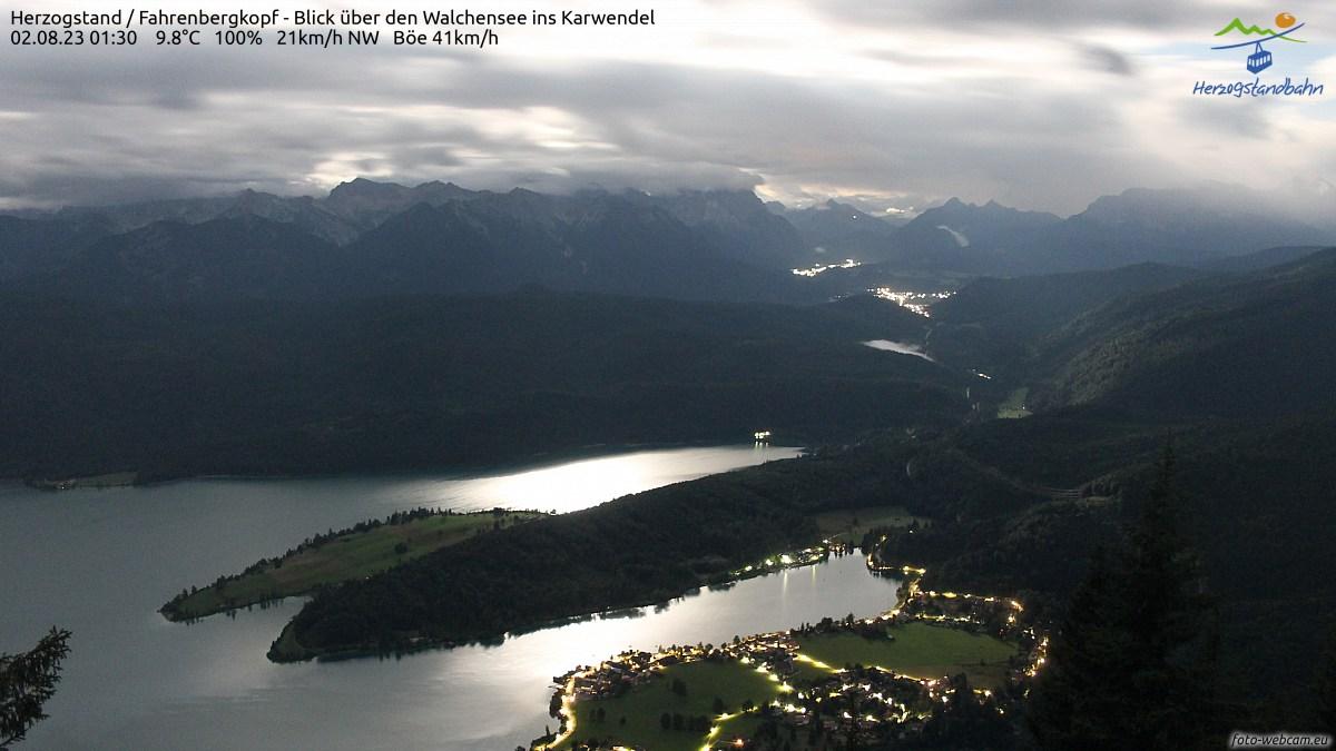 Die Blickrichtung ist Süden. Im Vordergrund ist der westliche Teil des Walchensees, links ist das Karwendel und rechts das Wettersteingebirge. Etwas rechts von der Mitte liegt das obere Isartal mit den Ortschaften Wallgau, Krün und Mittenwald. - zum Original - bitte 2* klicken